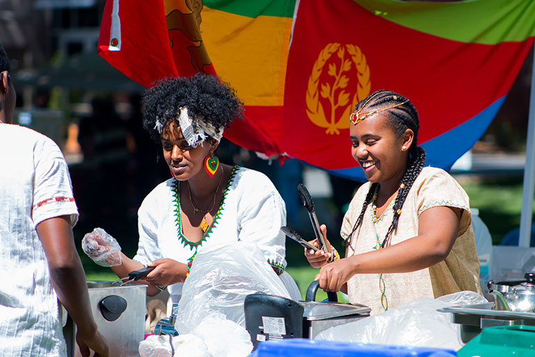 Two women serving food to festival attendees.