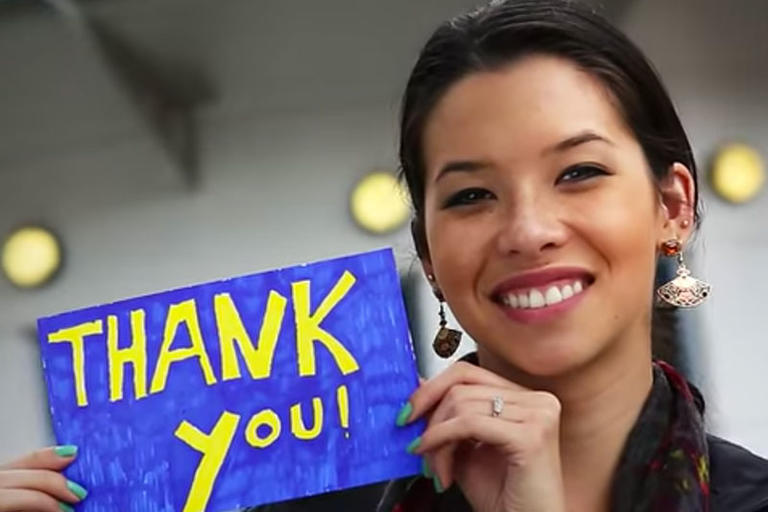 Female holding a thank you sign for donors.