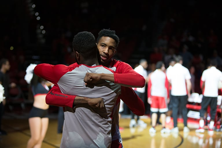 Two male basketball players hugging each other.