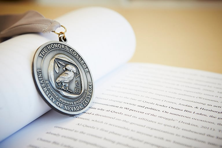 An honors medallion resting on an open textbook.