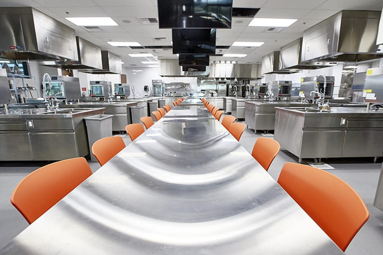 Large executive-style kitchen with stainless steel appliances and tables, a large table spans the aisle between cook stations