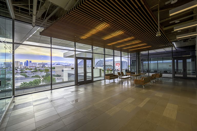 Open lounge area with floor to ceiling windows that overlook the Las Vegas Strip