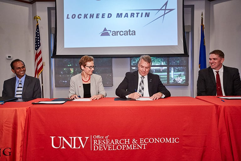 A group of people signing an agreement with Lockheed Martin