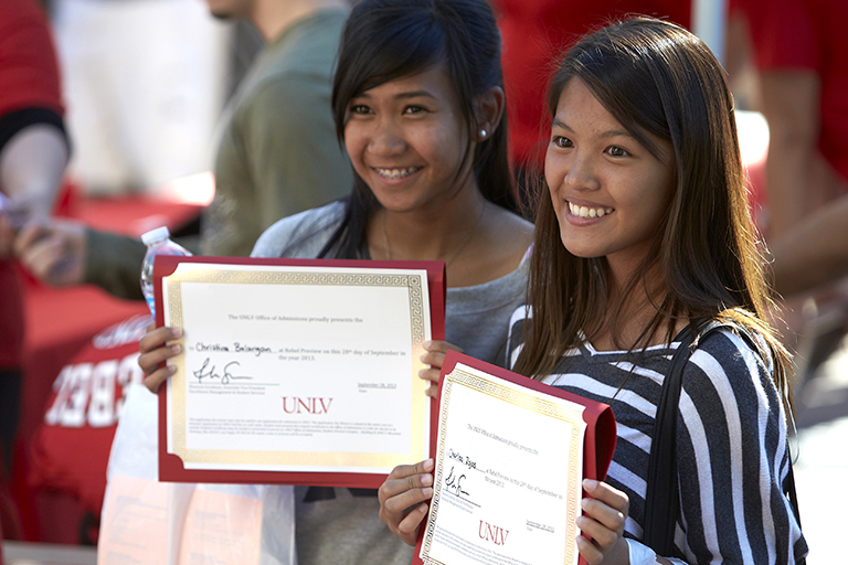 Two students holding up certificates