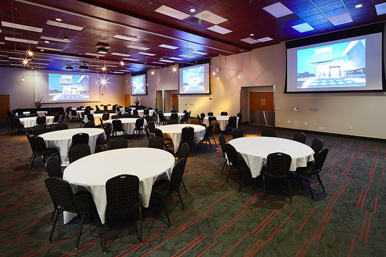 Large ballroom with numerous round table evenly spaced out, each table has a white table cloth and black chairs