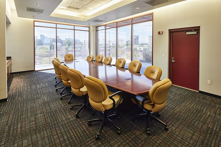 Large wood conference table surrounded by large plush office-style chairs, the back corner of the room has floor to ceiling windows overlooking the Las Vegas Strip