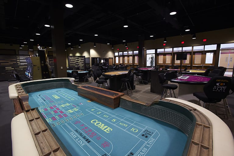 Large room with various tables for gambling including craps and a few slot machines