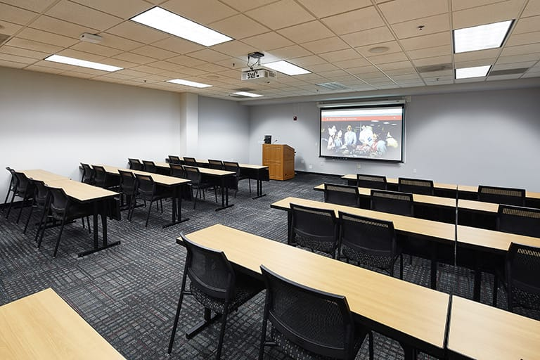 Large classroom with desks arranged into rows with an aisle down the middle