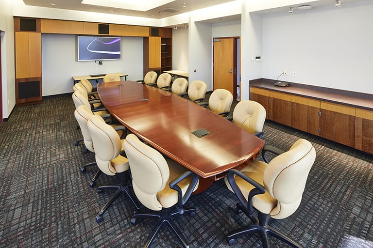 Large wood conference table surrounded by large plush office-style chairs