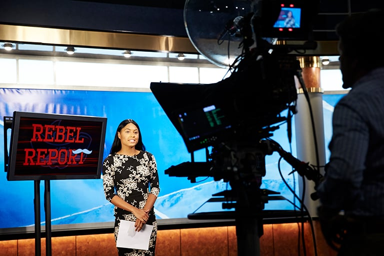 A student giving the Rebel Report in a news studio.