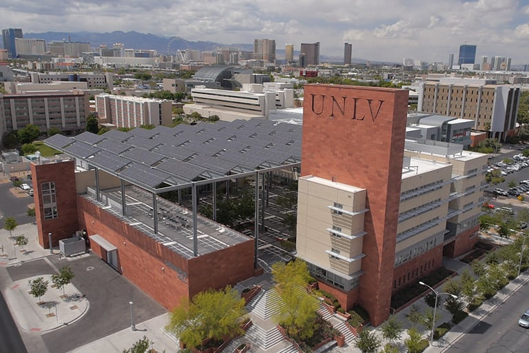 An aerial view of campus with the Strip in the background and Greenspun Hall in the foreground.