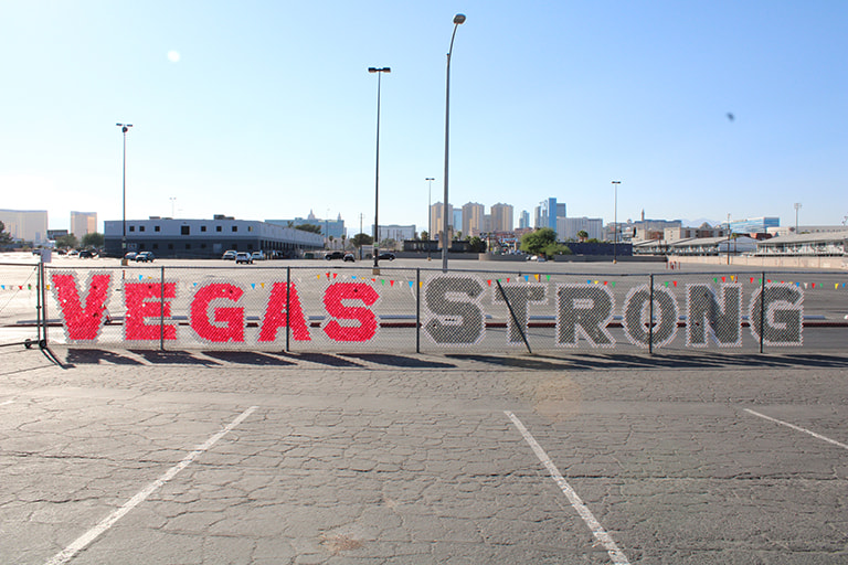 UNLV parking log where the word Vegas Strong is formed with cups in a chainlink fence.