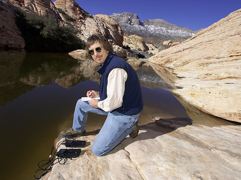 Scientist doing testing at a lake.