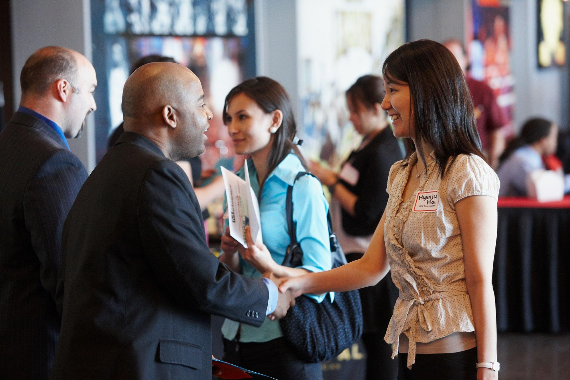 Man shaking a woman's hand in a group.