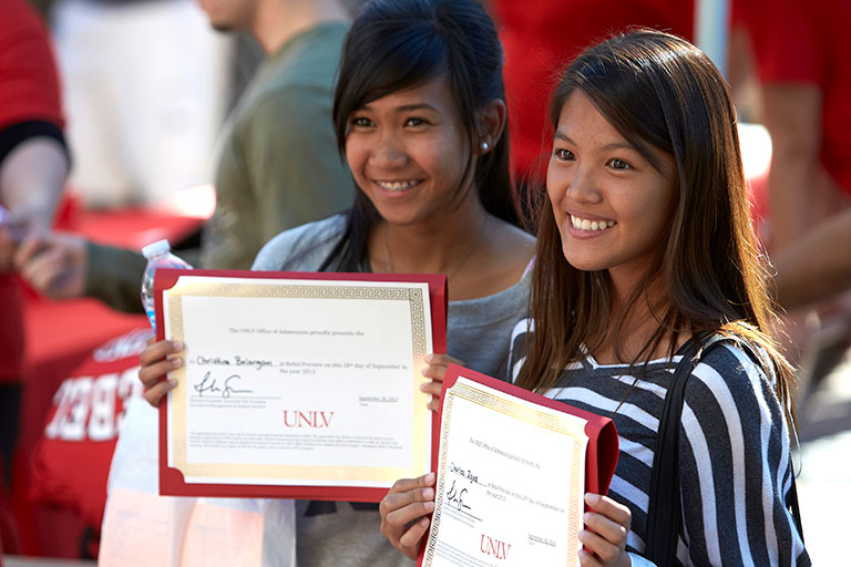 Two students holding gift vouchers