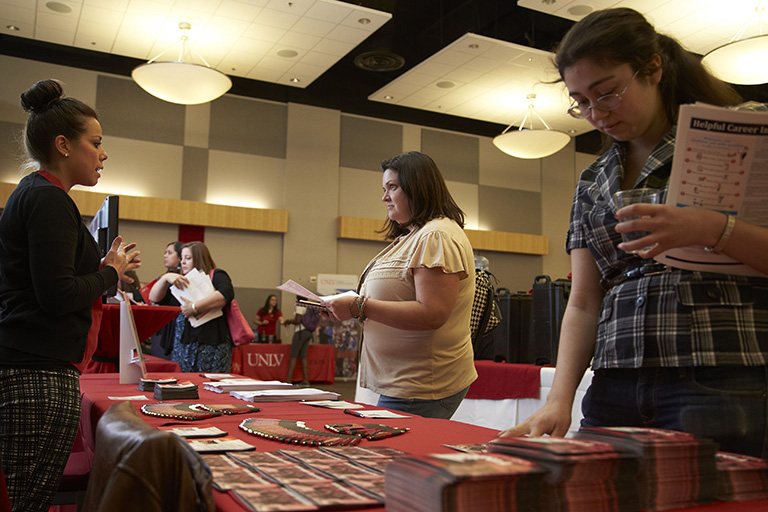 students looking at Advising Center table at convention