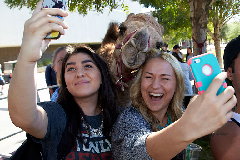 Student take a selfie with a camel.