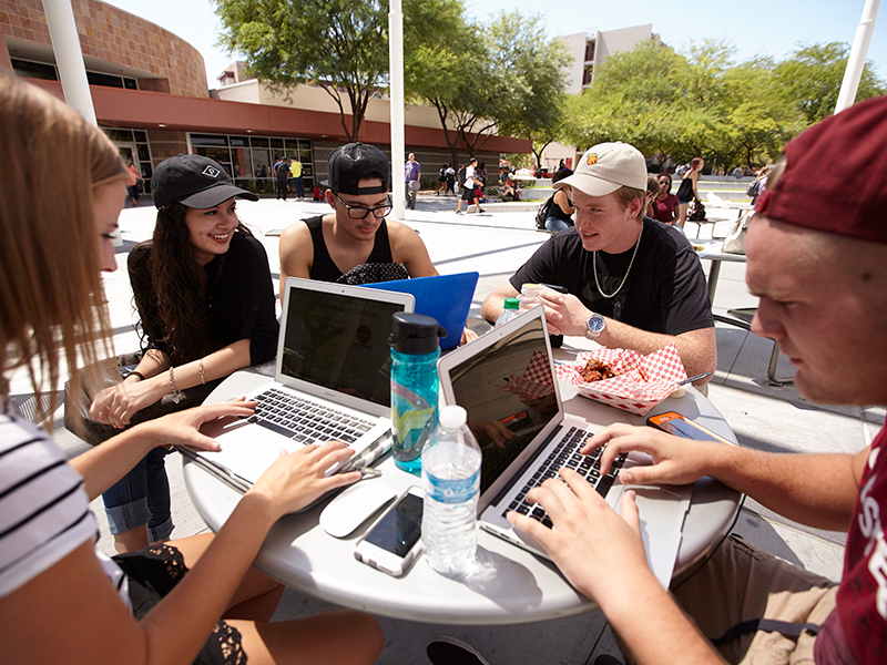 "alt=""A group of students sitting down at a table"""