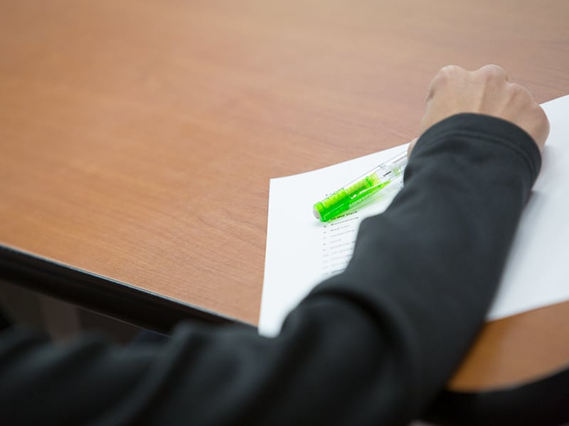 Student writing notes on a sheet of paper.