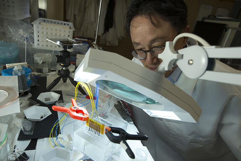"alt=""Male scientist examining his work through a microscope"""