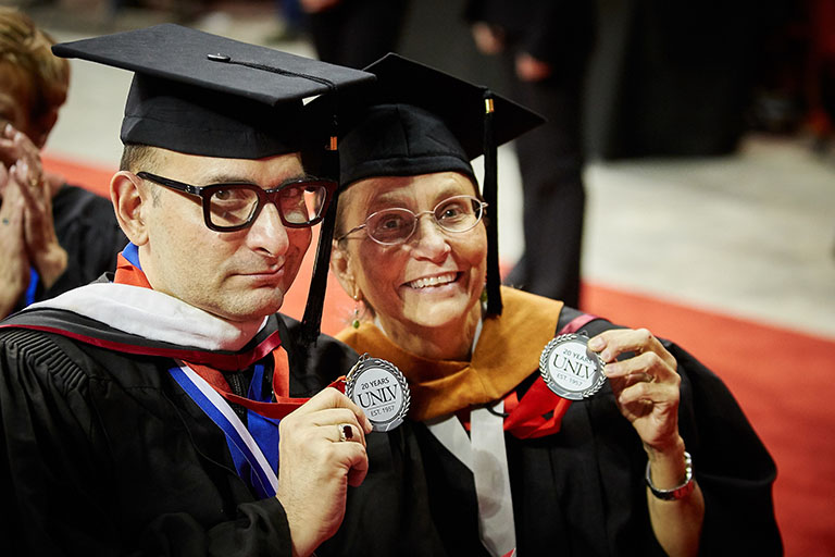 Two graduates hold up badges.