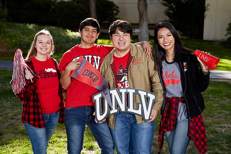 "alt=""Students holding a UNLV logo on campus."""