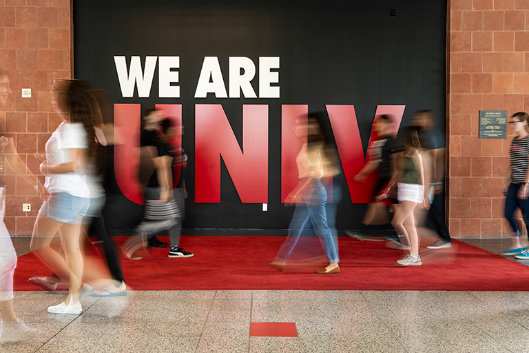 Students walking in front of a sign that reads We Are U.N.L.V.