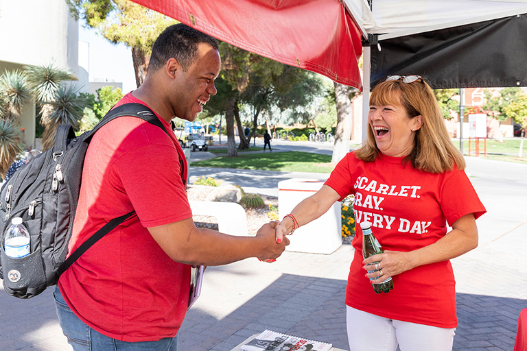 President Meana works a Welcome Week Booth