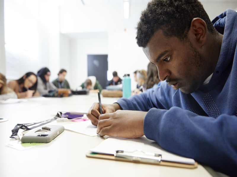 Student writing with pen while in class with other people
