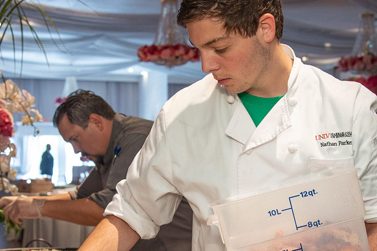 Student placing food at a catering table