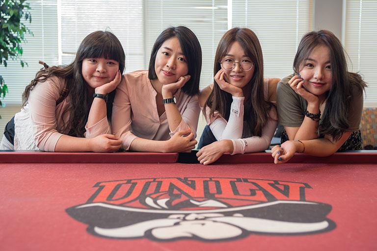 "alt=""Four girls smiling"""