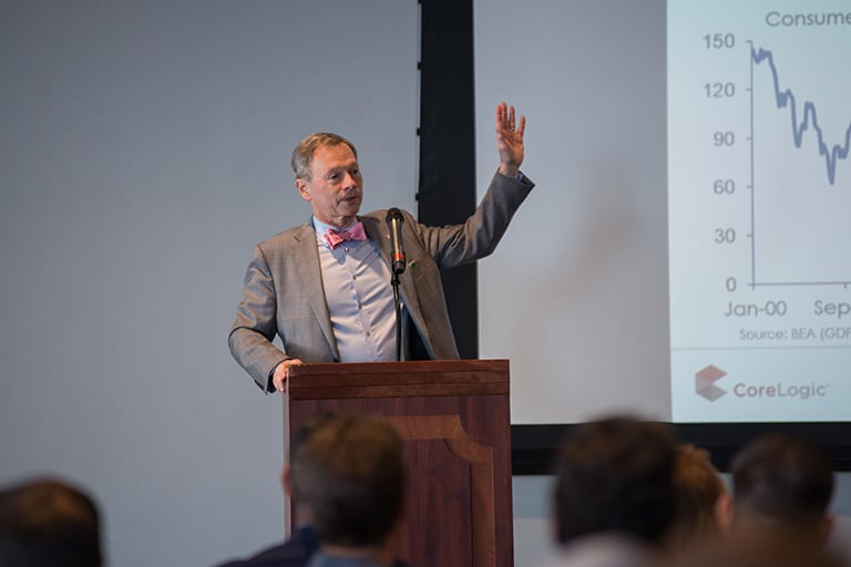 A man giving a lecture at a podium with statistics projected behind him.
