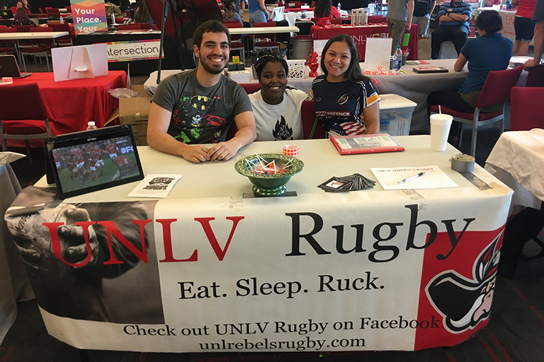 "alt=""UNLV members sitting down at a table"""