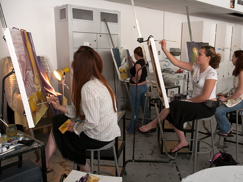"alt=""Multiple students painting on a canvas."""