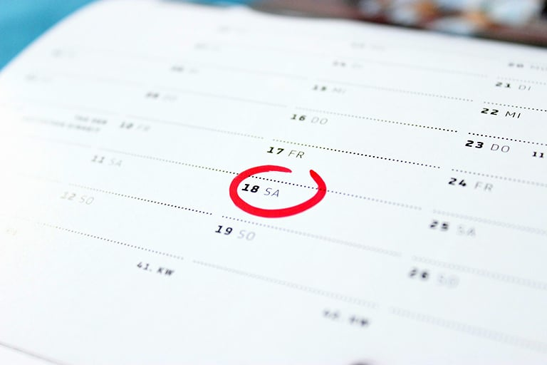 "alt=""A calendar with a date circled in red marker."""