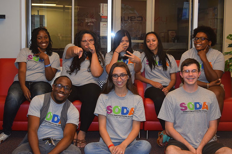 A group of students wearing S-O-D-A shirts, posing for a picture.
