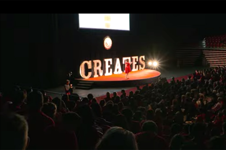 An auditorium full of guests watching a speaker on a giant stage with enlightened letters spelling