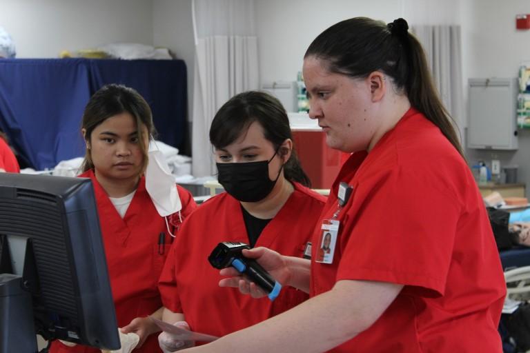 Nursing students looking at monitor