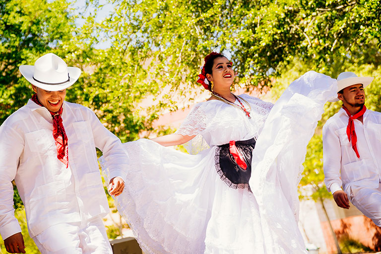 Two male dancers in white suits with red bandanas around their necks, and one female dancer in a white dress.
