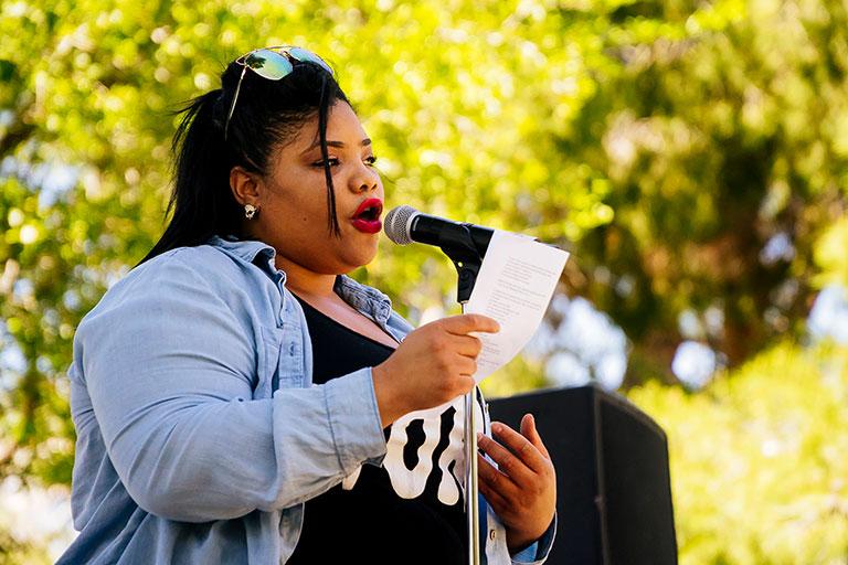 Student giving a speech outdoors.