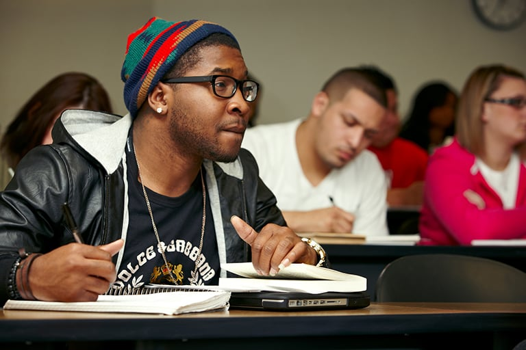 "alt=""Student looking ahead attentively while taking notes"""