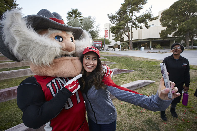 "alt=""A student taking a selfie with ""Hey Reb"" on U-N-L-V campus."""