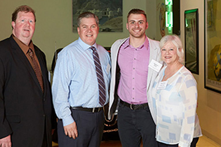 "alt=""Vladislav had the opportunity to meet leaders from the Comprehensive Cancer Centers of Nevada at the Charter Class Scholarship Mixer on August 2.  From left to right - James Kildea, Practice Director of Operations; Jon Bilstein, Executive Director; Vladislav; and Mary Ann K. Allison, MD, President."""