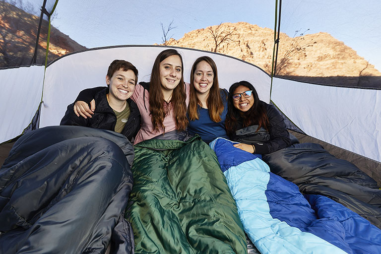 Four students in a tent and sitting in sleeping bags.