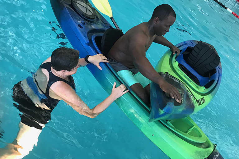 Trainer with a student on a kayak in an indoor pool.