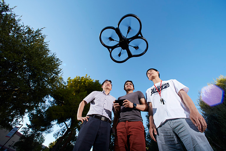 Students on campus using a remote controlled aerial drone.