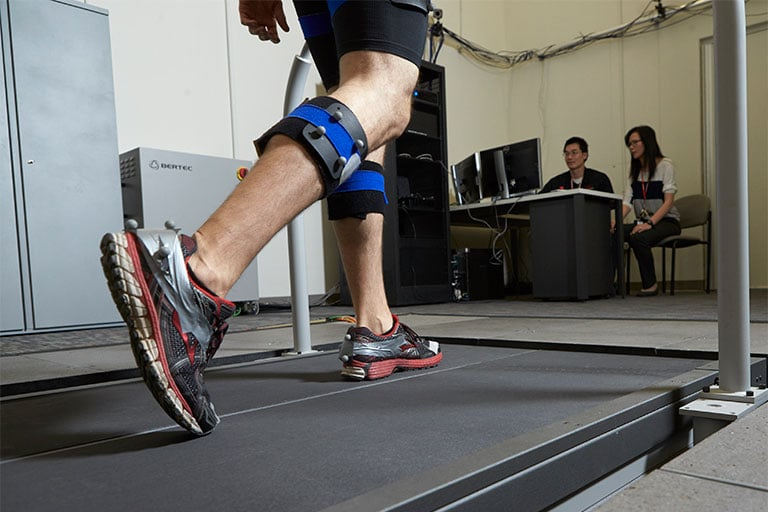 Person walking on a large treadmill with devices around his legs