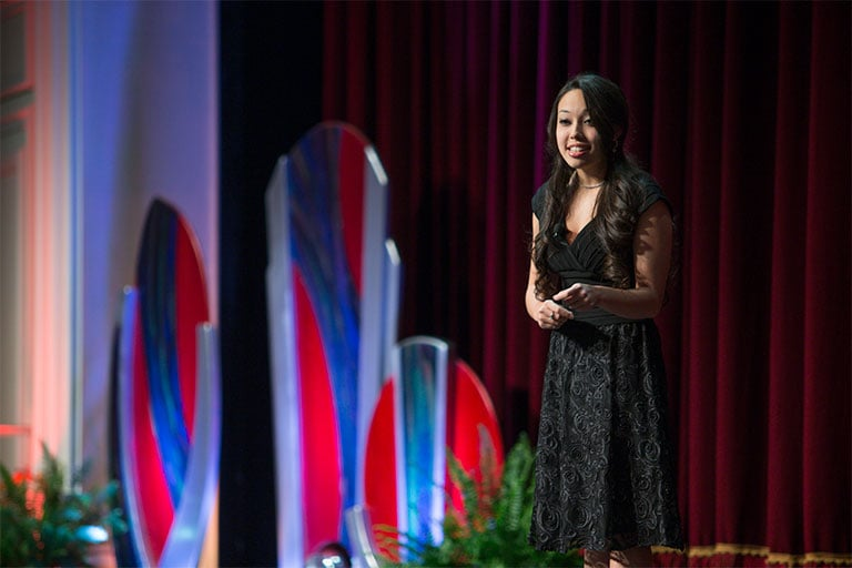 Young woman speaks at a fundraising event.