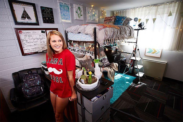 Female student shown in her dorm room.