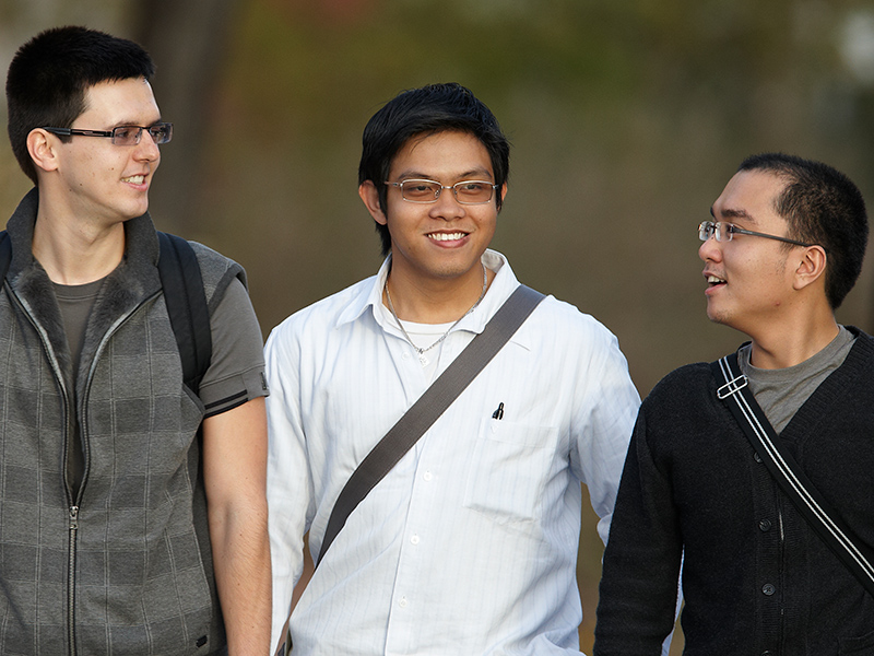 Three students walking through campus
